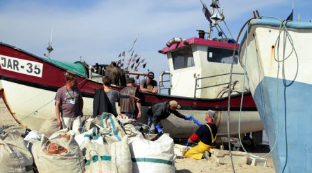 Fishermen in an exchange next to two beached vessels